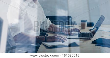 Double exposure concept.Adult bearded businessman working at wood table in modern place.Attractive middle age man using notebook.Skyscraper office building on the blurred background.Wide