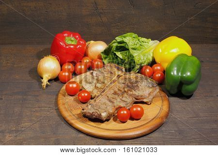 Grilled T bone steak mitRosmarin with tomatoes onions and pepper garnished on a rustic wooden chopping board