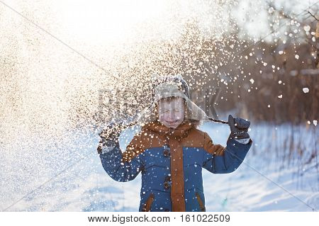Winter little child playing throws up snow outdoors during snowfall. Active outoors leisure with children in winter on cold snowy days.