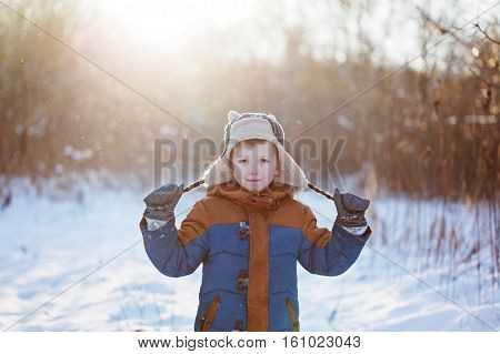 Happy little child playing throws up snow outdoors during snowfall. Active outoors leisure with children in winter on cold snowy days.