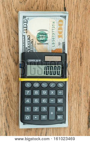 Black small calculator rubber band strapped with a bundle of dollars