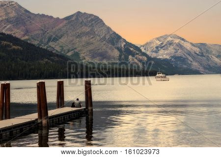 image of an evening sun setting behind the mountains reflecting on the lake with a man sitting on wooden pier and a boat sailing in the distance in the summer time.