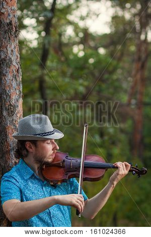 Violinist playing the violin outdoors ciose up