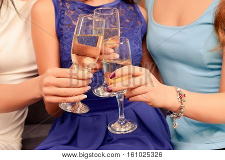 Close up of three women holding glasses with champagne and clinking