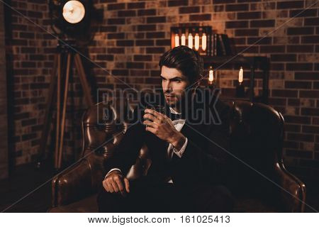 Handsome Young Man In Elegant Suit With Glass Of Whiskey Relaxing On Sofa