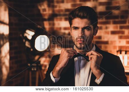 Portait Of Confident Handsome Man Corecting His Bow Tie And Wearing For Event Party