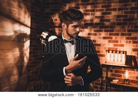 Handsome Businessman In Black Suit Fastening Buttons On The Sleeves In Loft