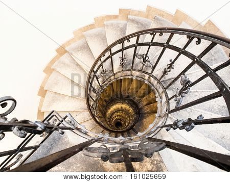 Upside view of indoor spiral winding staircase with black metal ornamental handrail. Architectural detail in St. Stephen's Basilica in Budapest, Hungary