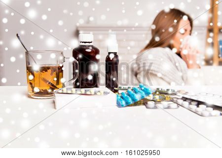Sick woman cup of tea pills and mixture on snowy winter background