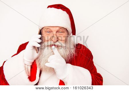 Portrait Of Happy Santa Claus Talking On Phone And Showing Shh Gesture