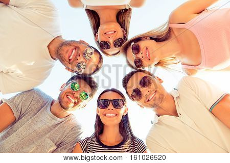 Group Of Happy Young Friends  Enjoying Summer Day And Looking Down On Camera