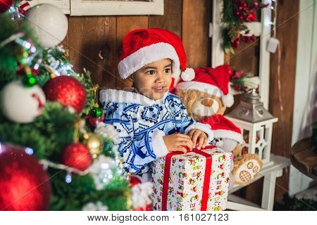 African American boy dressed costume Santa Claus near Christmas tree with a gift. Christmas and New Year