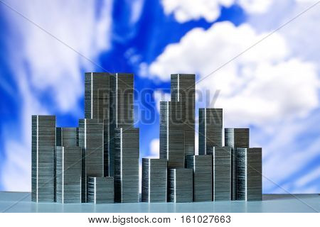 Staples arranged to form city skyline on a blue sky with white clouds background
