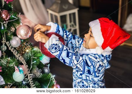 African American boy dressed costume Santa Claus Christmas tree decorated with toys. Christmas and New Year