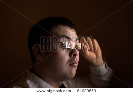 Young attractive businessman alone at night sitting at computer laptop watching porn or online gambling which reflecting in his glasses isolated on black background on internet chat addiction concept. poster