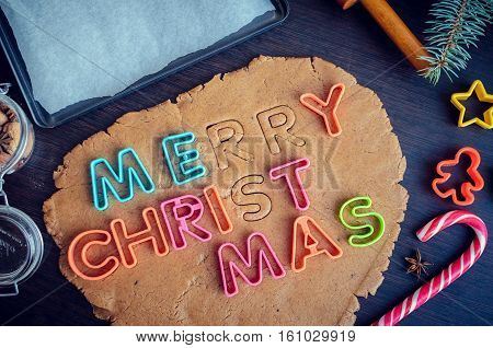 Cutters letters on a dough. Phrase Merry Christmas. Step of making traditional Christmas gingerbread cookies. Raw dough and cutters for the holiday cookies on a dark table. Top view.