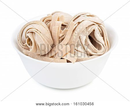 Dry homemade rolled traditional italian pasta in bowl isolated on white background. Raw fettuccine or tagliatelle or pappardelle.