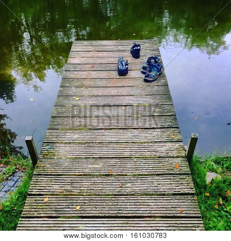 Two pair of boys shoes standing on the pier of a lake