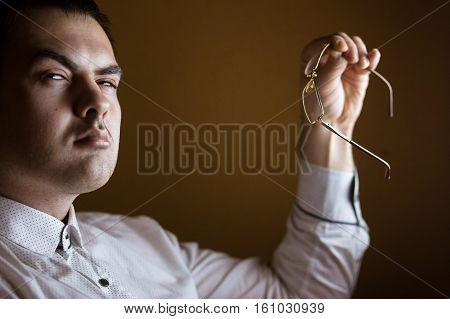 Handsome attractive businessman holding glasses i and looking with reproach to camera