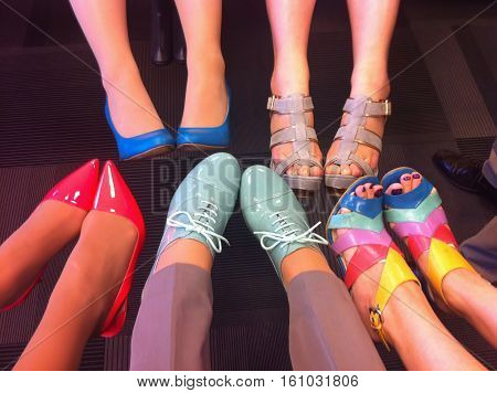 Female legs in fashion shoes. Colorful fashion shoes on feet. Shoes in blue mint red beige and multicolored. Heel shoes and boots on women. Formal shoes in office. Colorful office wear. Shoe image