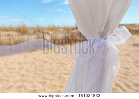 Wedding ribbon in the wind. Against the backdrop of the sea and the beach.