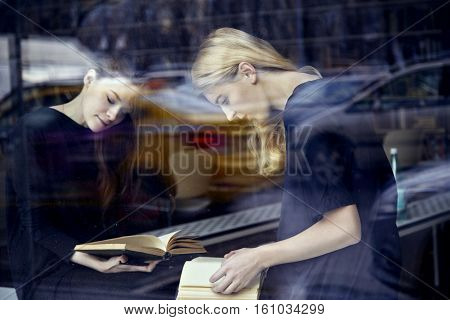 Two young students women in a library reading book. Sitting near window. Education concept