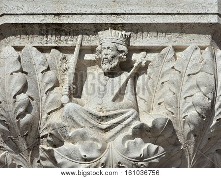 Trajan emperor relief as medieval king with sword and scepter on doge palace capital in Venice