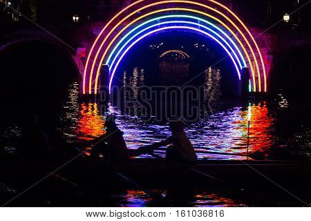 Rowers pass by the artwork 'Bridge of the Rainbow' by Gilbert Moity in a canal on the boat route Water Colors during the Amsterdam Light Festival 2016