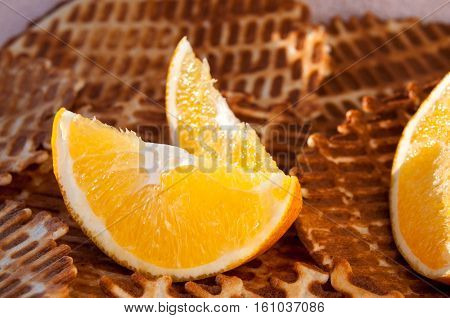 Two Lobules Of Orange On A Background Of Crispy Waffles Close-up Две дольки апельсина на фоне хрустя