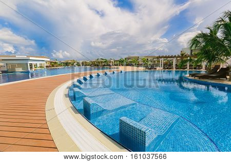 Cayo Guillermo island, Iberostar Playa Pilar hotel, Cuba, June 28, 2016, nice beautiful inviting view of a curved comfortable swimming pool with ceramic pool beds and people relaxing, in background