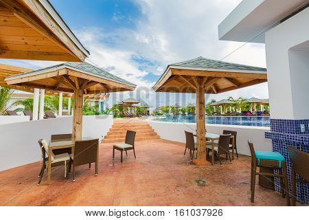 Cayo Guillermo island, Iberostar Playa Pilar hotel, Cuba, June 28, 2016, nice fragment of view of comfortable swimming pool and pool bar sitting area with people relaxing, swimming in background