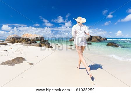 Happy woman wearing white loose tunic over bikini and beach hat, enjoying amazing white sandy beach on Mahe Island, Seychelles. Summer vacations on picture perfect tropical beach concept.