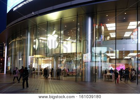 BEIJING - FEBRUARY 23: People walking in front of Apple store on Wangfujing street in Beijing, China. This store is Asia's biggest Apple store with 2,300 square meters, February 23, 2016.