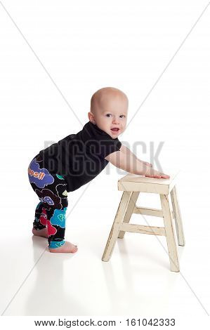 A seven month old baby boy leaning on a bench for support as he learns how to stand. Shot on a white seamless background.