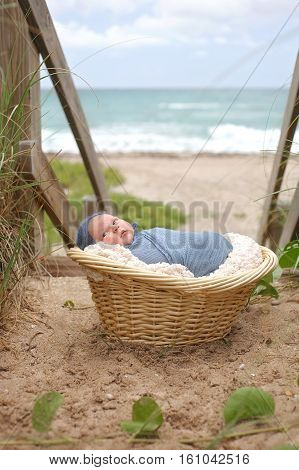 An alert three week old newborn baby boy swaddled in a blue wrap and lying in a wicker basket on a beach.