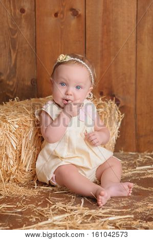 A six month old baby girl wearing a yellow dress. She is sitting and leaning against a small straw bale. Shot in the studio on a wood paneled floor and background.