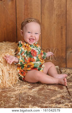 A smiling six month old baby girl wearing a floral romper in fall colors. She is sitting and leaning against a small straw bale. Shot in the studio on a wood paneled floor and background.