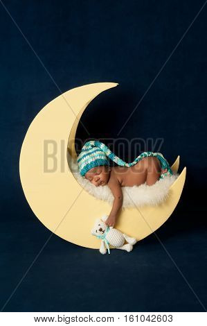 Studio portrait of a four week old newborn baby girl wearing a stocking cap and leg warmers. She is sleeping on a moon shaped posing prop and holding a crocheted Teddy bear.