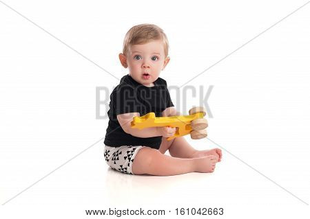 An eight month old baby boy playing with a wooden toy. Isolated on a white background.