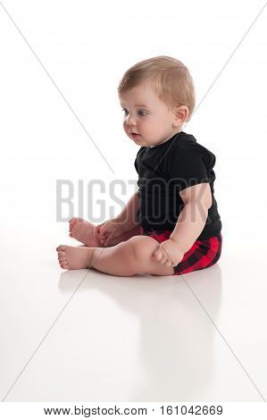 An eight month old baby boy sitting on white seamless background.