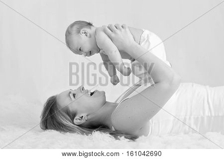 A black and white image of a mother laughing and playing with her baby boy.