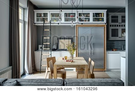 Kitchen in a modern style with gray walls, white lockers and shelves with accessories. There is a wooden table with chairs, dark ladder, fridge with metal doors, sofa, sink with faucet, hanging lamps.