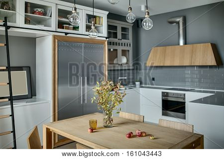 Cool kitchen in a modern style with gray walls, white lockers and shelves with accessories. There is a wooden table with branches in a vase and chairs, ladder, fridge, sink, oven, stove, kitchen hood.