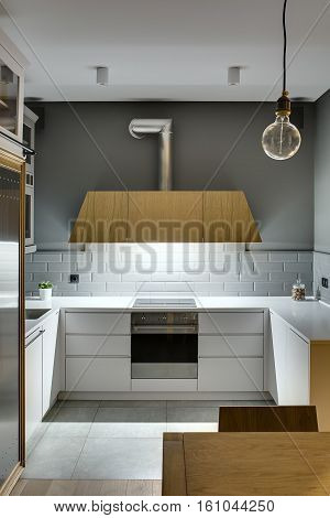 Design kitchen in a modern style with gray walls and white lockers and shelves. There is a glowing wooden kitchen hood, stove, oven, sink, fridge, wooden table with a chair, plant in the pot, lamps.
