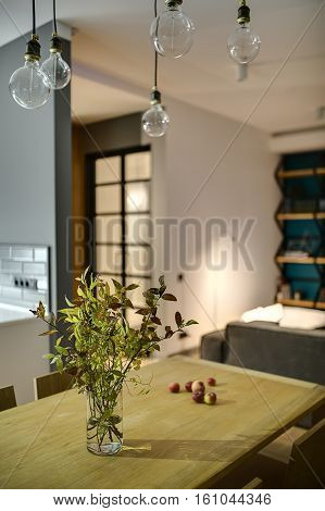 Green branches in a vase and apples on the wooden table with chairs in the modern interior. There is sofa, shelves on the blue wall, glowing lamps, hanging lamps. Closeup. Wide aperture photo.