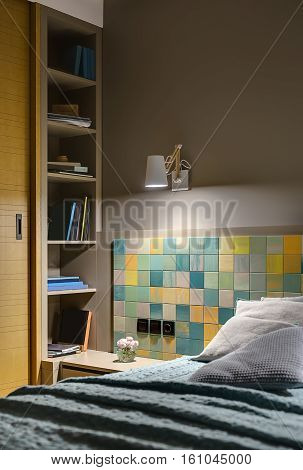 Bed with several pillows and a coverlet on the background of the colorful tiles with black switches and a power socket. There is a wooden nightstand with flower, shelves with books, glowing lamp.