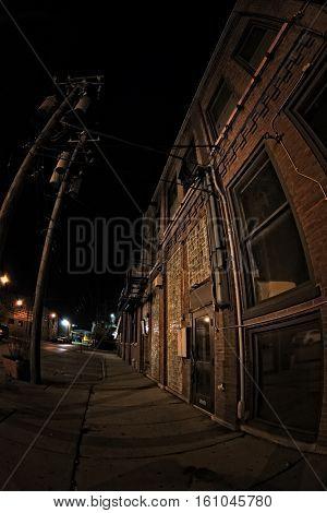 Dark urban downtown city sidewalk and building at night.