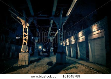 Dark urban downtown city alley at night with car garage doors and elevated train tracks.