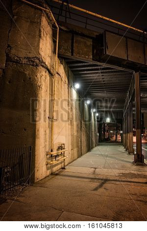 Dark urban downtown city elevated train underpass and sidewalk at night.
