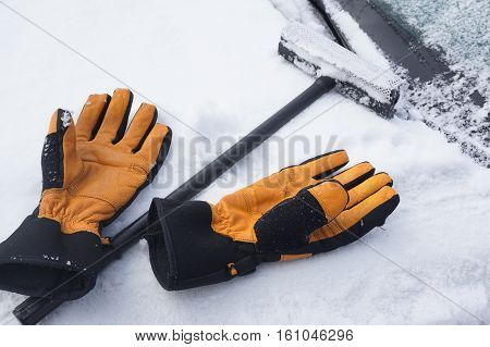 removing snow and ice on the car windshield with gloves, ice scraper and broom